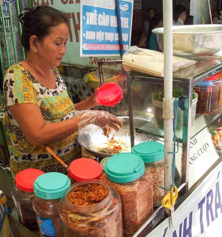 Lady preparing banh trang tron at a street food stall in Vietnam